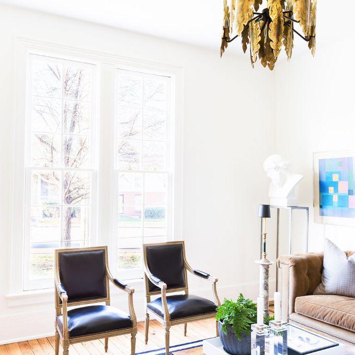 La sala de estar cuenta con una alfombra a rayas y un candelabro dorado con forma de pluma