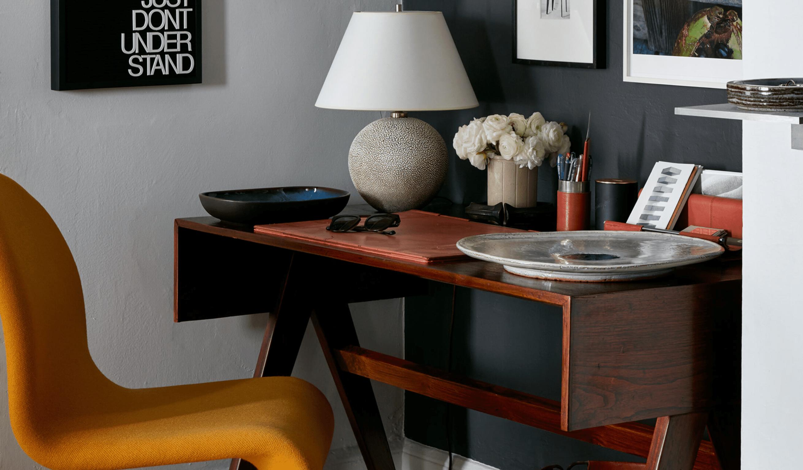 An antique midcentury modern desk placed alongside a contemporary desk chair