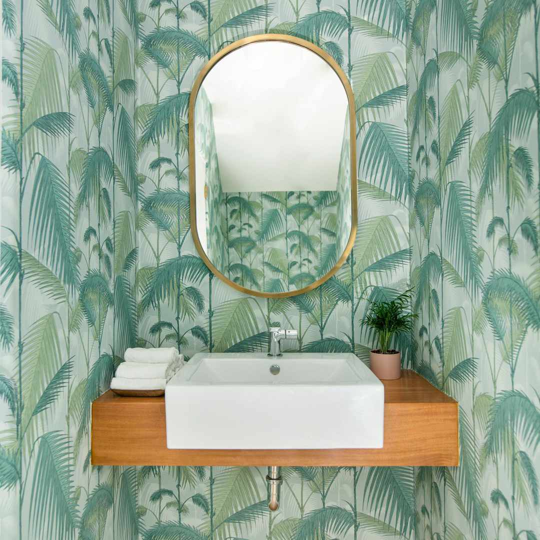 A powder room lined with vibrant tropical print wallpaper