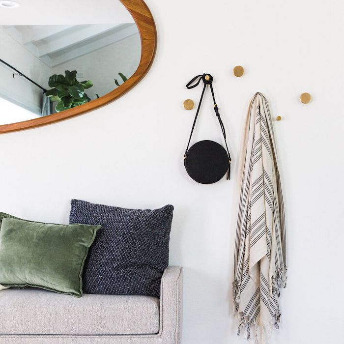 entryway with circular hooks, soft bench, oblong shaped mirror