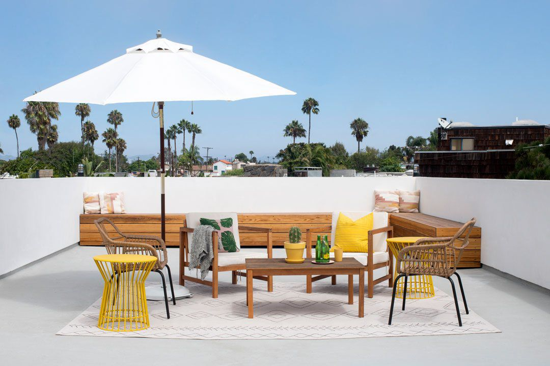 A rooftop deck outfitted with wooden furniture and a few yellow accessories