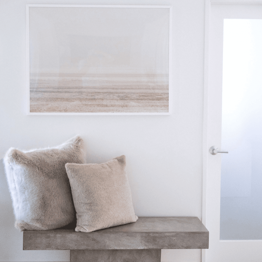 A wall decorated with a small cement bench and two beige throw pillows