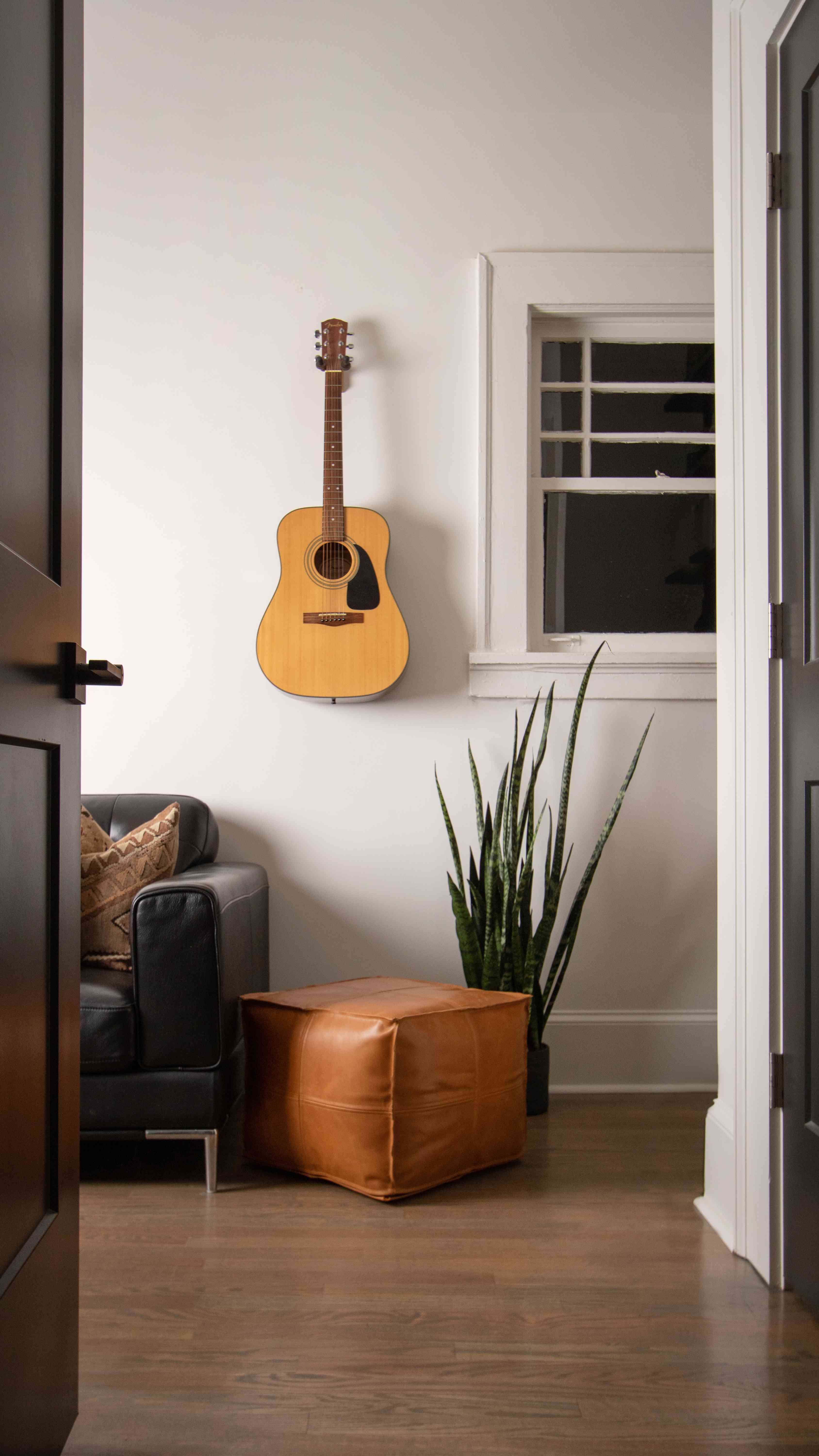 Guitar hanging on wall in living space.