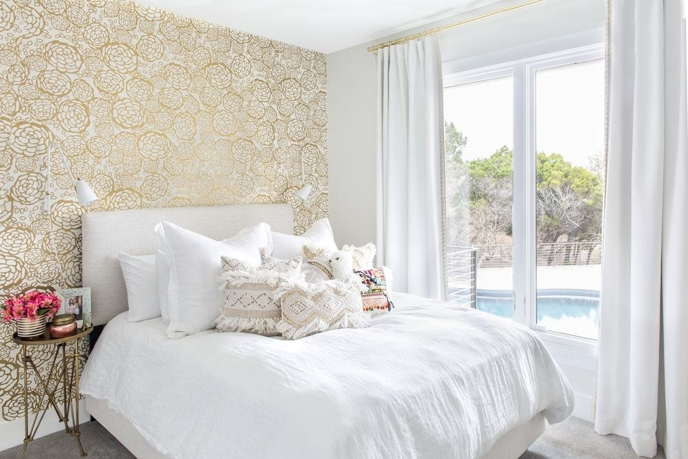 Bright white bedroom with gold wallpaper and luxe bed.