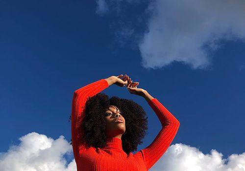 Una mujer en un suéter rojo levantando los brazos sobre su cabeza contra un cielo azul con nubes.