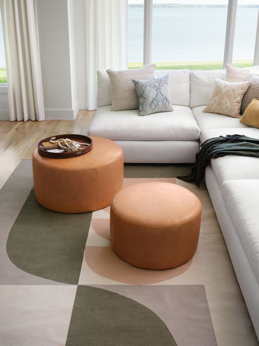living room with leather ottomans on a patterned rug next to a sectional sofa