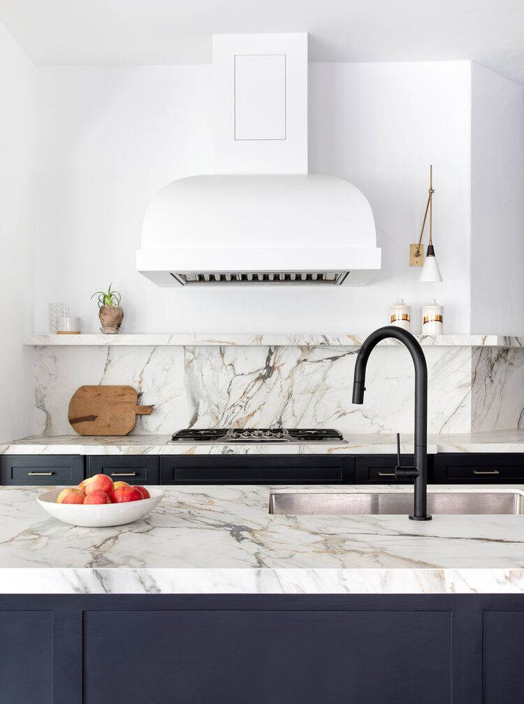 A kitchen with striated marble countertops and a matching marble backsplash