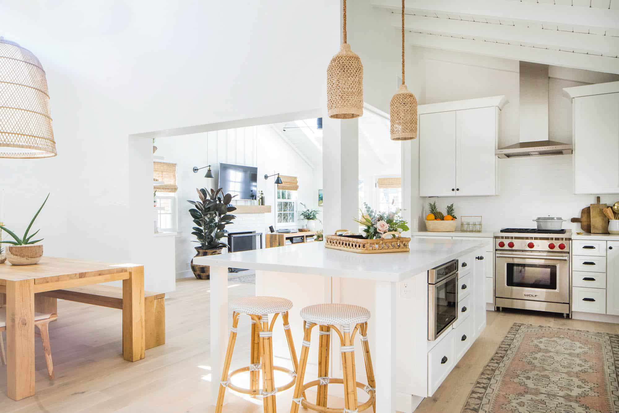 An open-concept kitchen with white and pink details