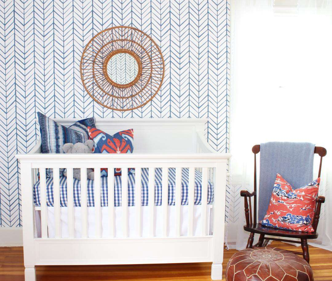 Bassinet with blue and white chevron wallpaper behind it.
