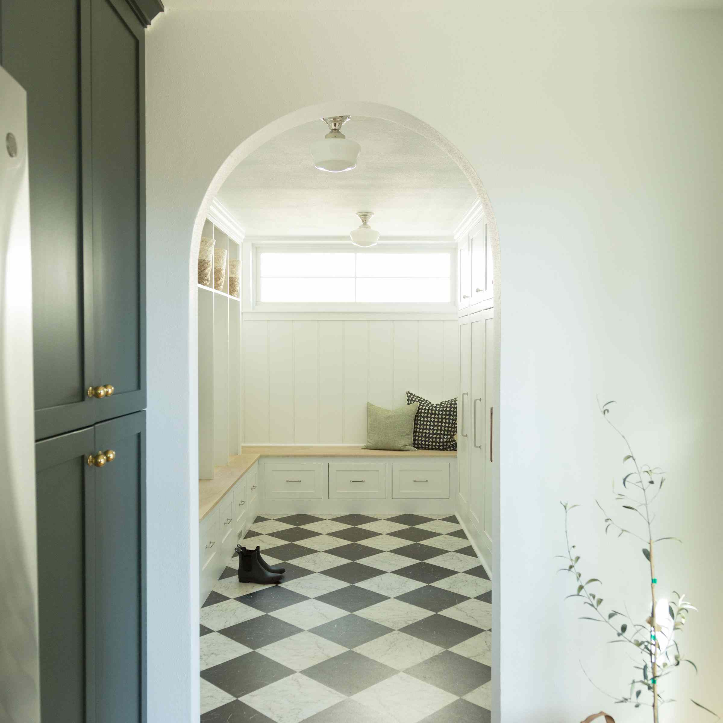 Chic mudroom with arch and checkered floor