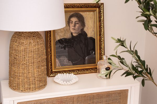 Rattan lamp and side table with vintage art.