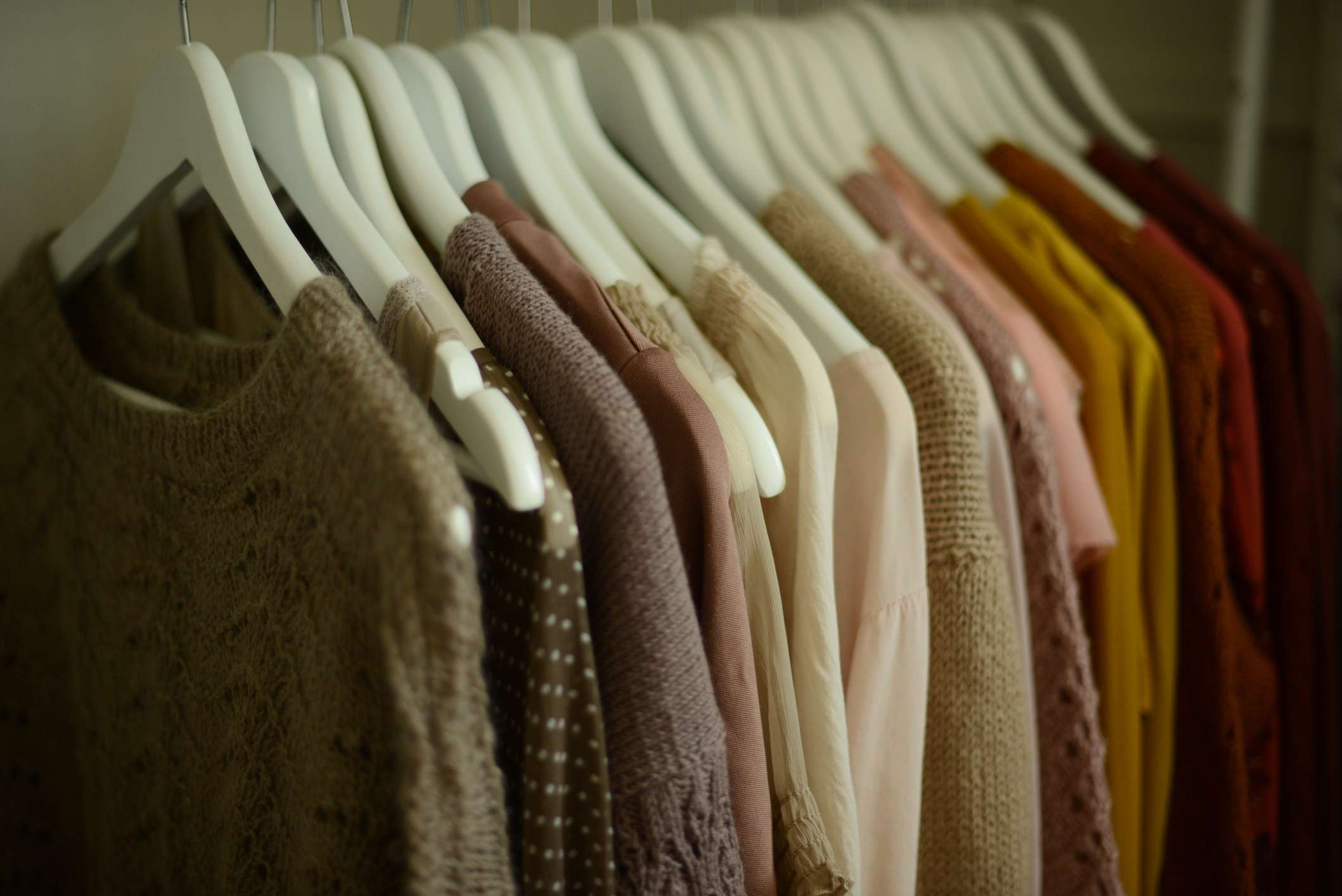 Color-coded sweaters and blouses on hangers