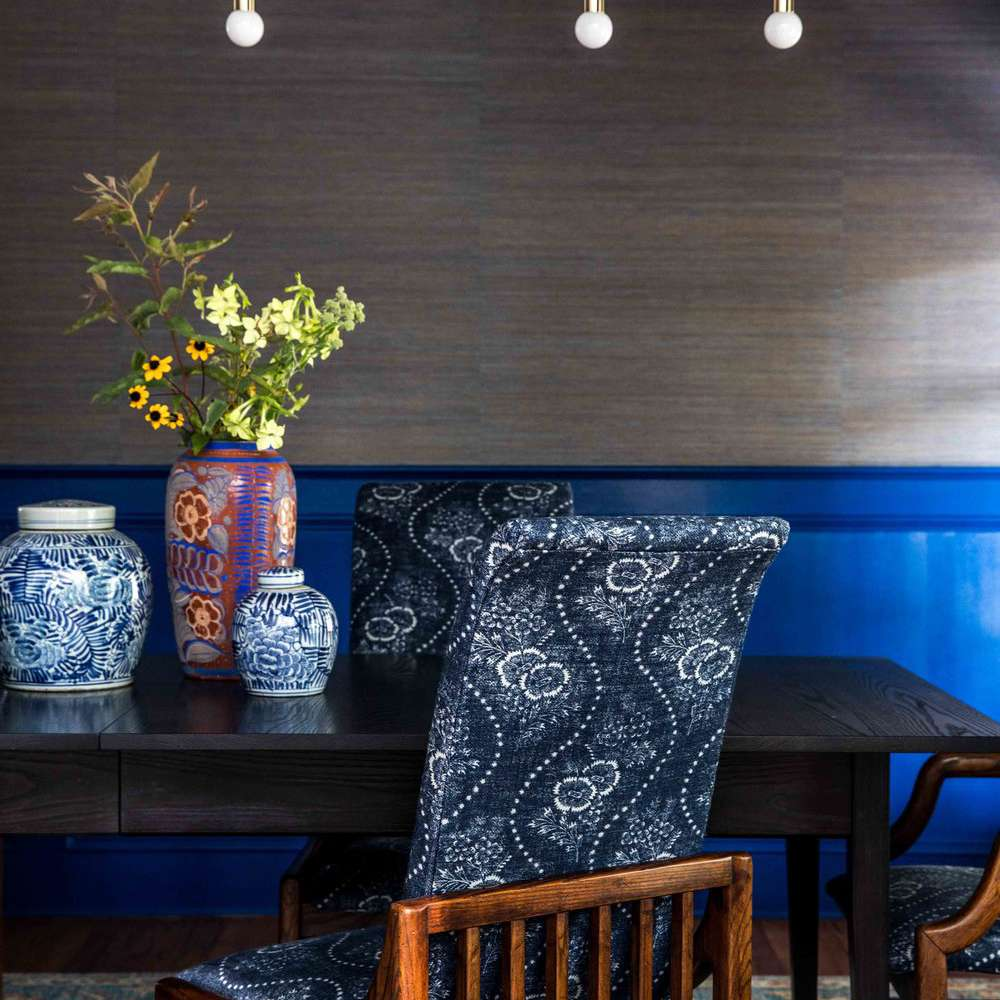 A dining room with dark blue walls, dark blue upholstered chairs, a light blue rug, and several vibrant blue vases on the table