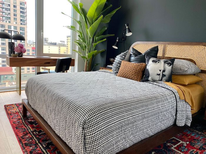 bedroom with black wall, windows with no curtains and a city view, black and white polka dot bedding with an multi-color accent rug underneath