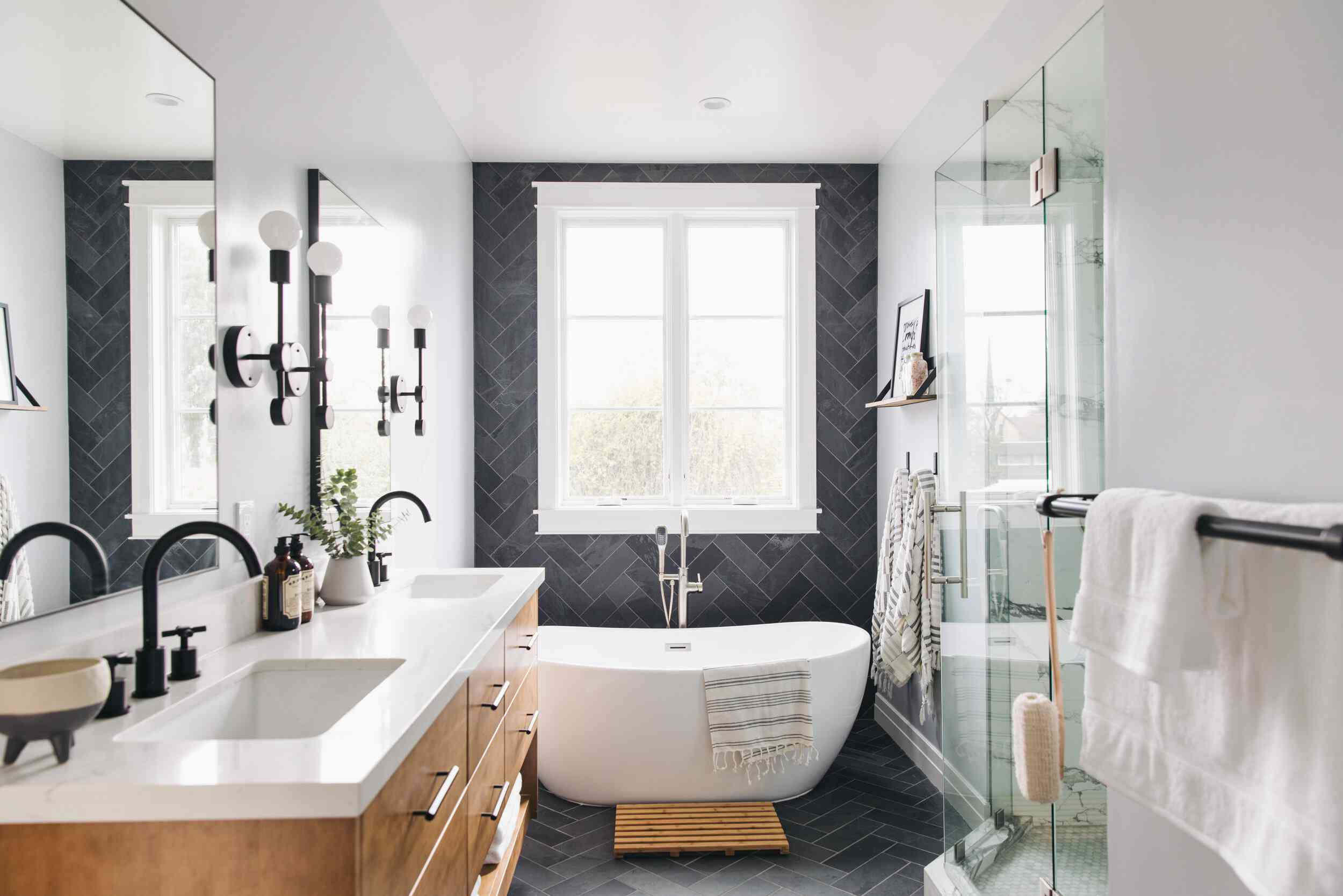 A bathroom with black tile-lined walls, a freestanding tub, and a double vanity