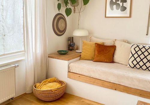 Boho daybed under a hanging plant.