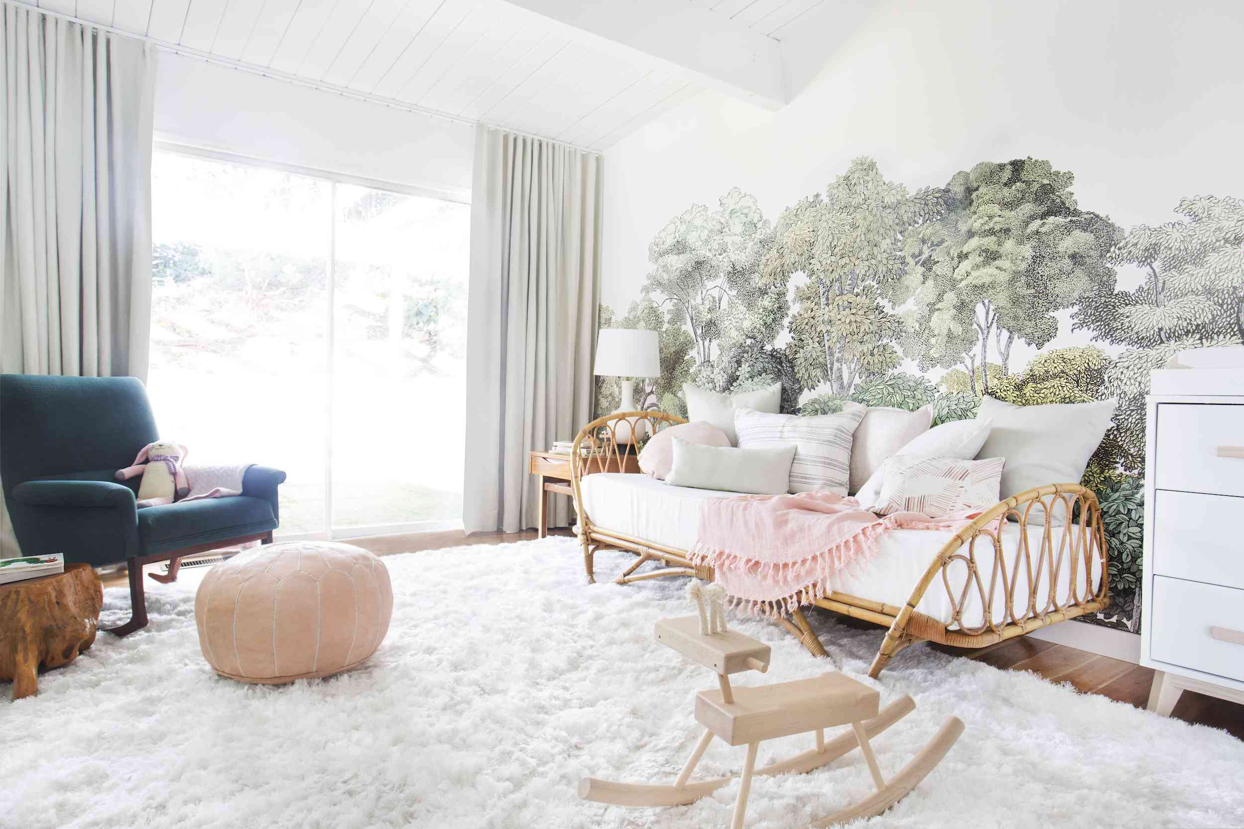 nursery with decorated wallpaper, daybed and chair in the corner