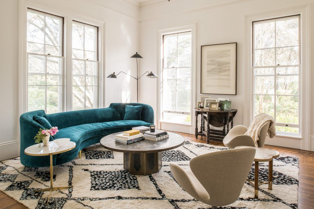 Small living room with teal sofa and patterned rug