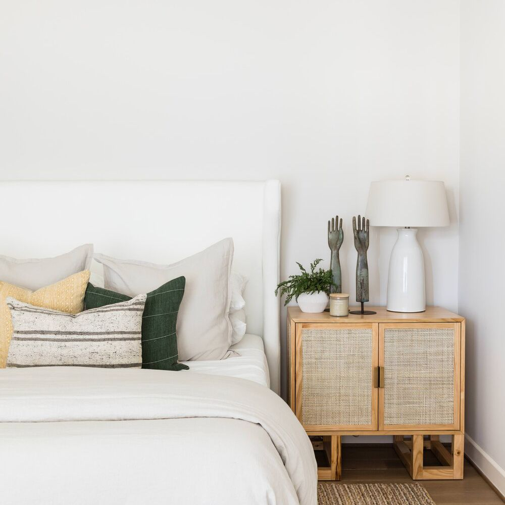 A sleek minimalist bedroom with a ceramic white table lamp