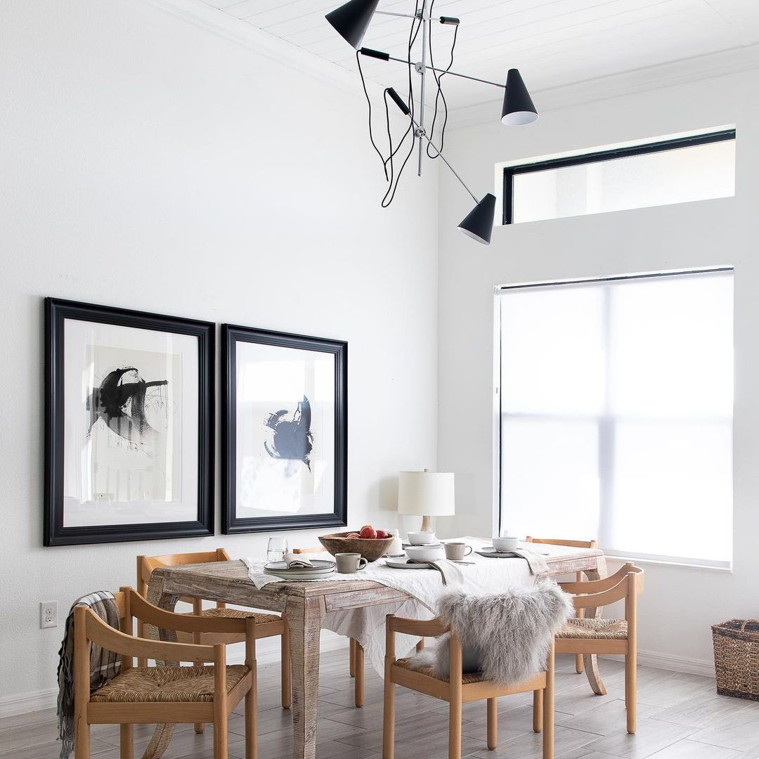 Minimalist dining room with high ceiling and modern black chandelier