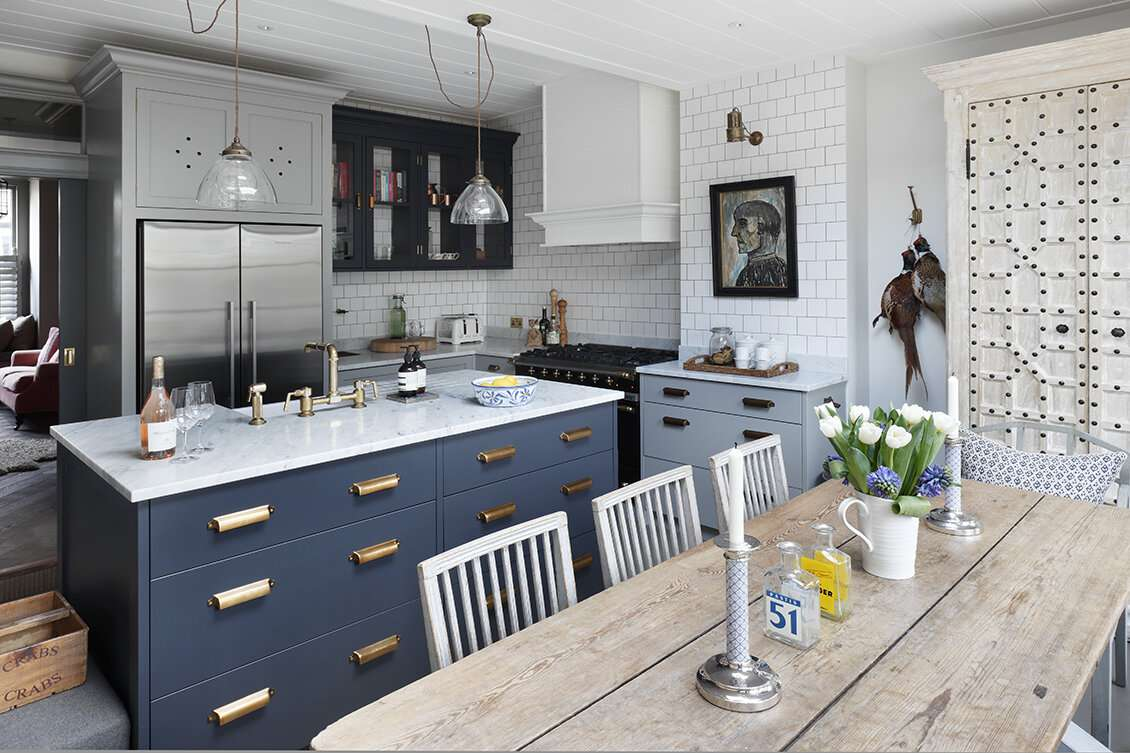 A kitchen with a navy bar and light blue cabinets