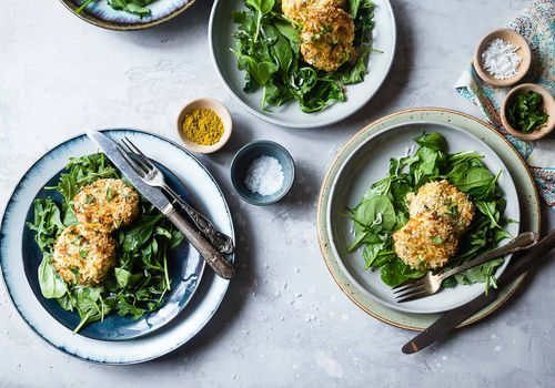 Salmon cakes served over greens on several plates