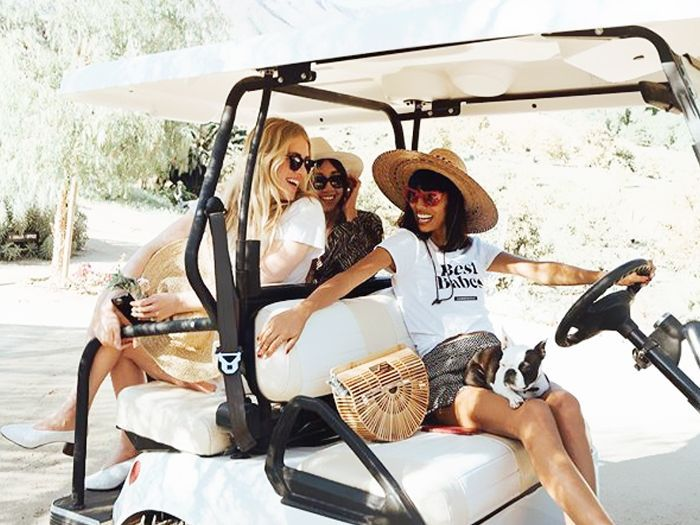 Group of three stylish young women in a golf cart, smiling at one another