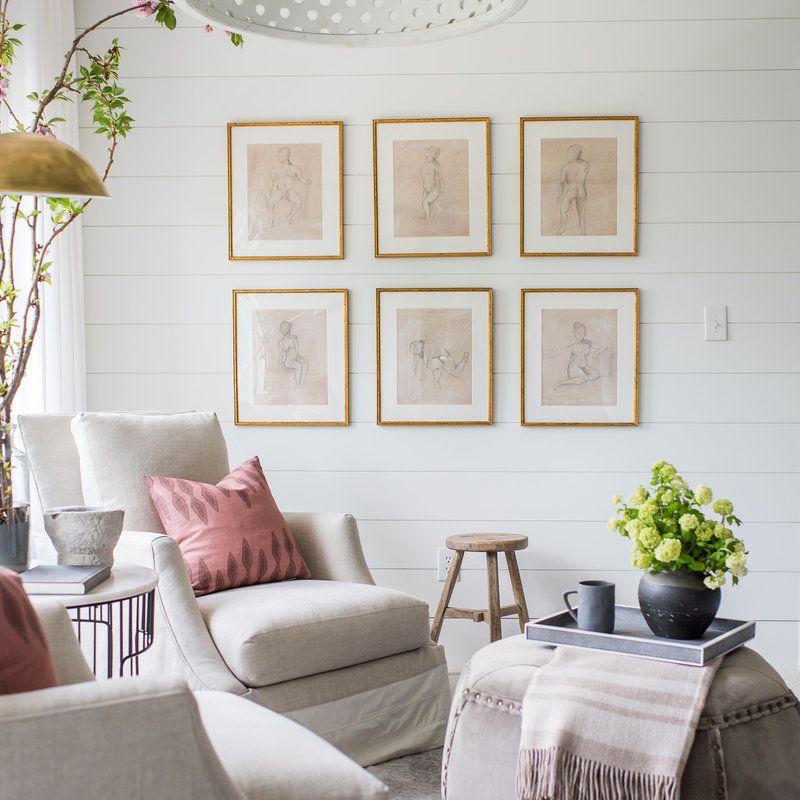 Neutral seating area with a gridded gallery wall of six figure sketches