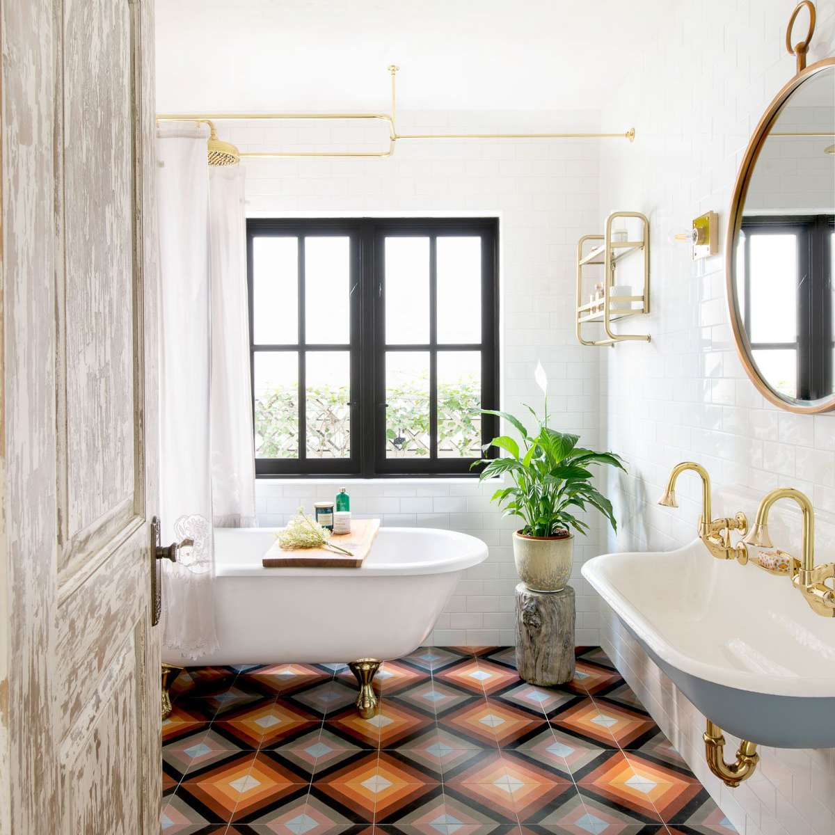 A maximalist bathroom with boldly tiled floors and a double sink