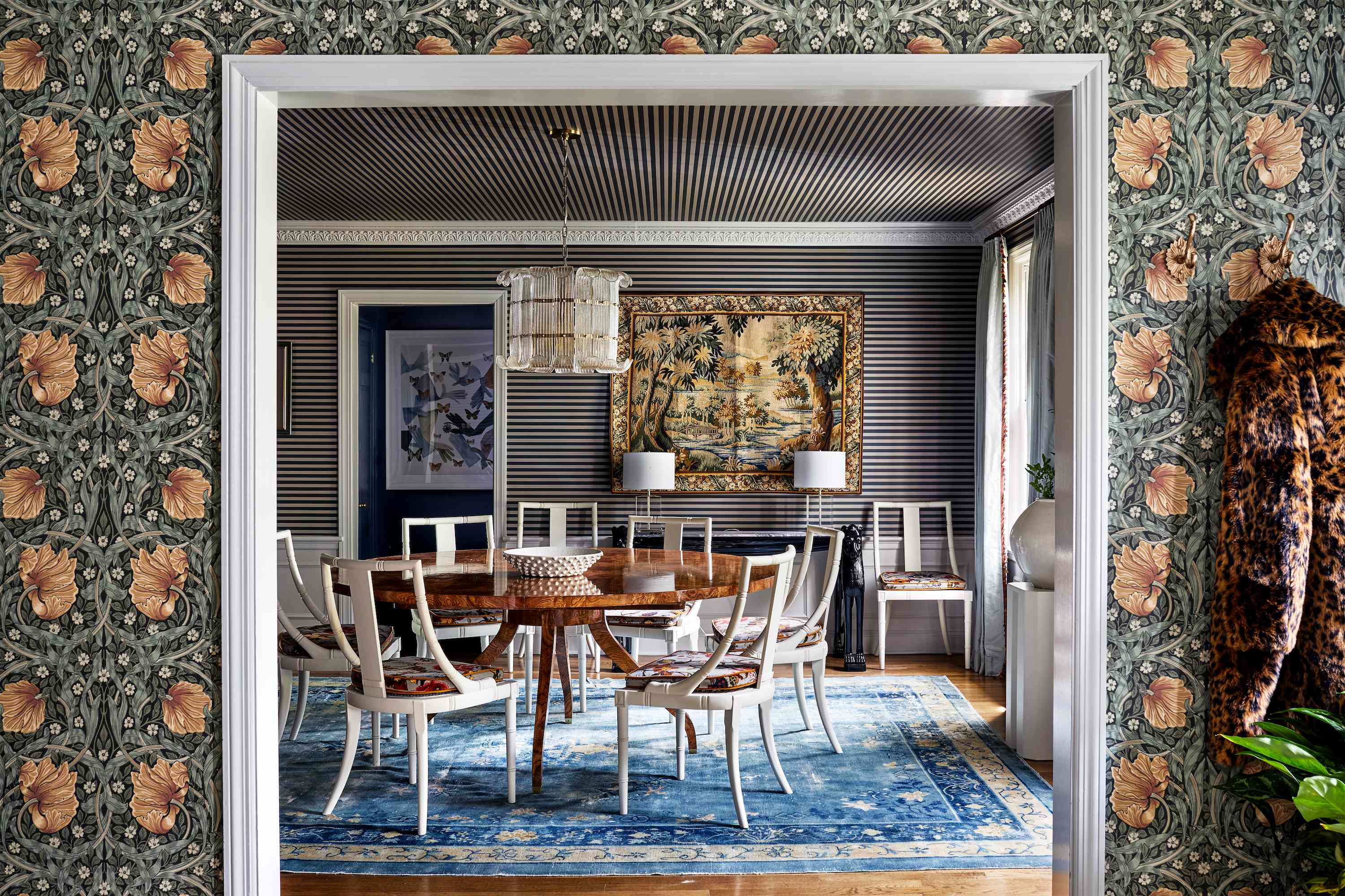Dining room with luxe wallpaper and traditional table.