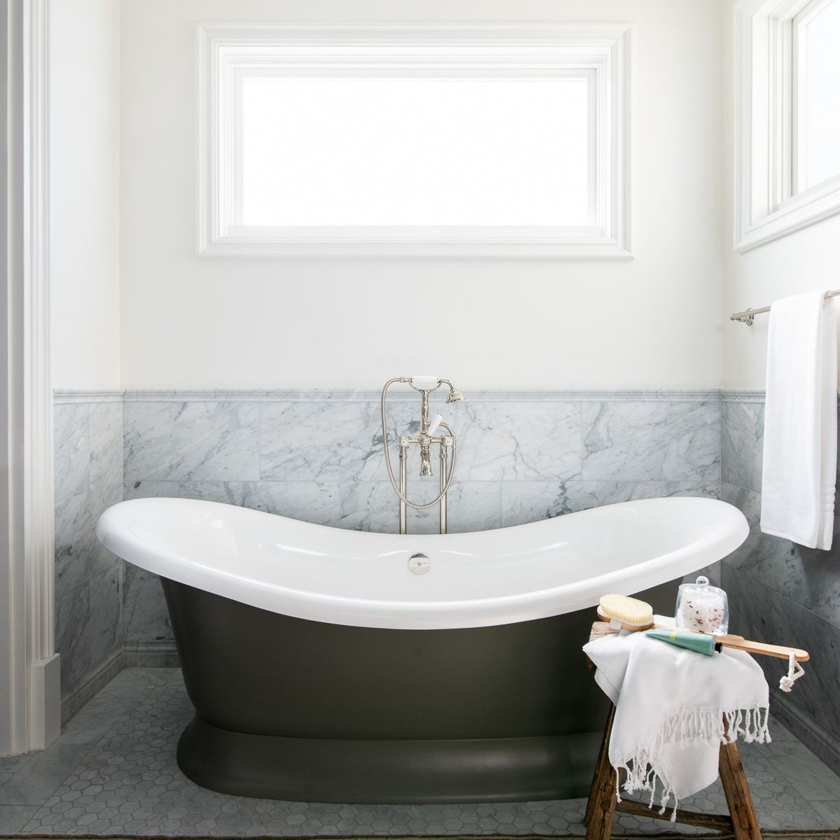 A bathroom lined with gray marble and a light brown printed rug