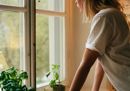 blonde woman looking out of a window, which has two plants and a lit candle on the windowsill