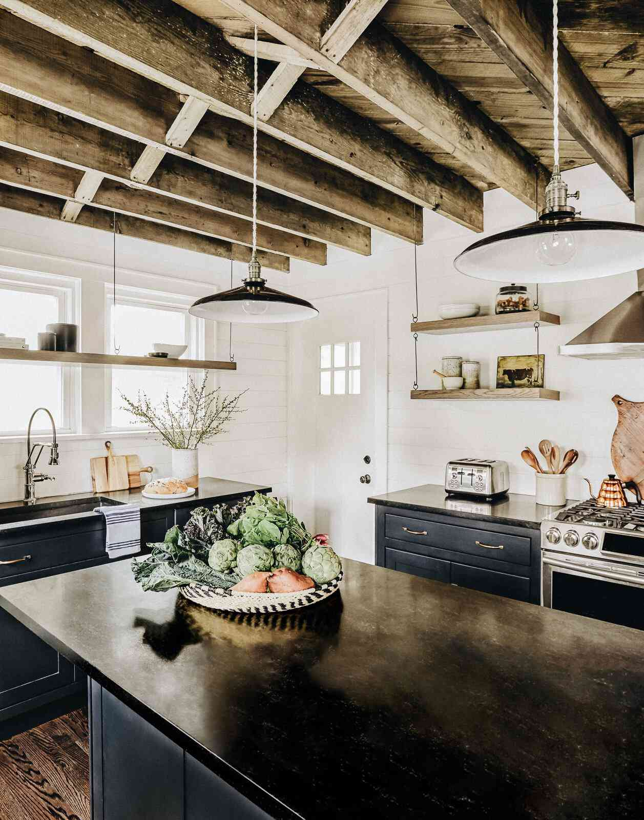 Kitchen with exposed wood beam ceiling, expansive kitchen island, dark-colored cabinetry