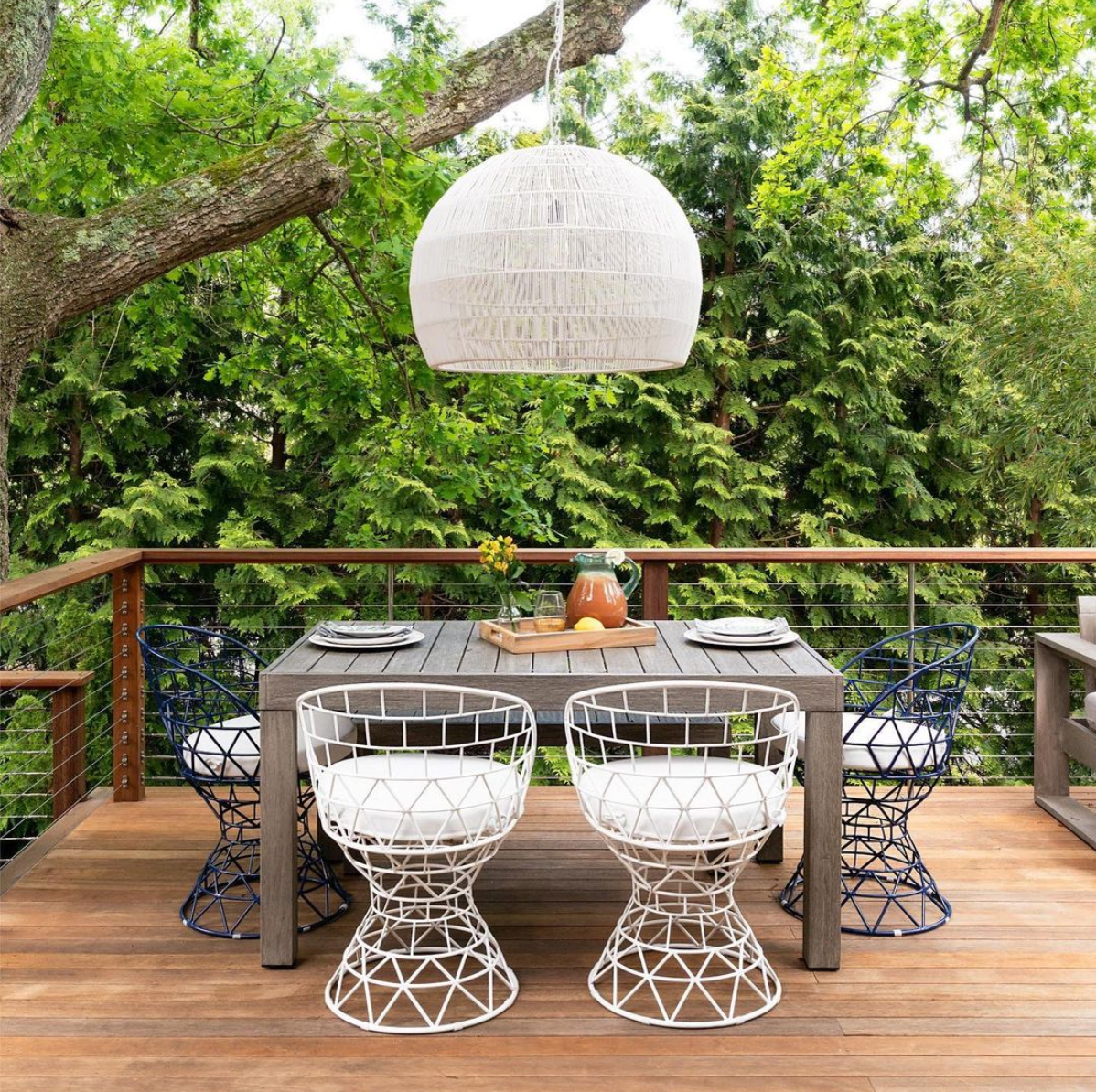 An outdoor dining room with several bold chairs and a large chandelier