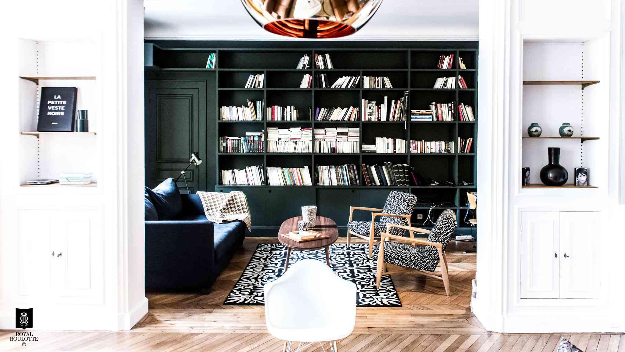Living room with wall of dark green bookshelves