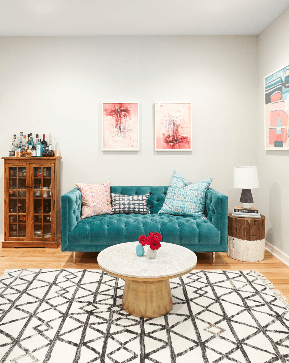Living room with hung artwork, teal tufted loveseat and patterned area rug