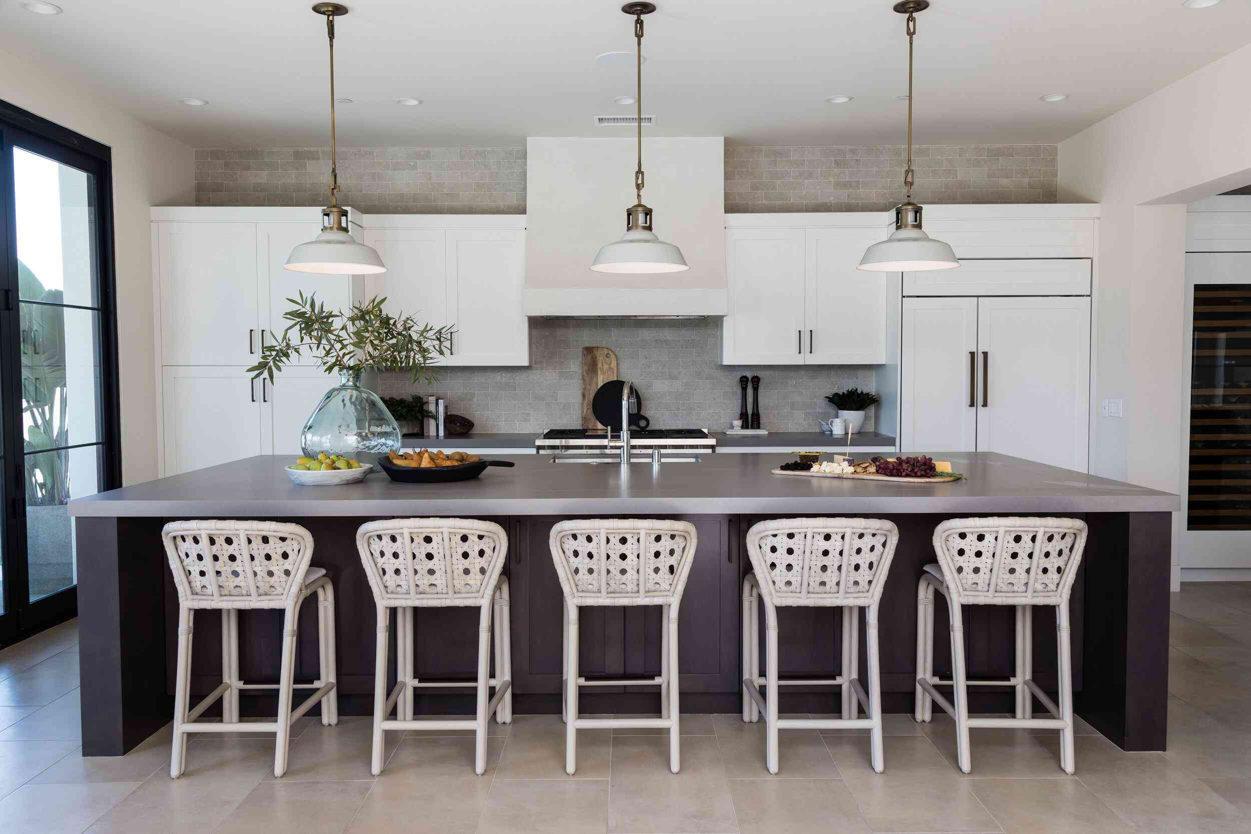 A kitchen with a gray backsplash, gray countertops, and charcoal cabinets