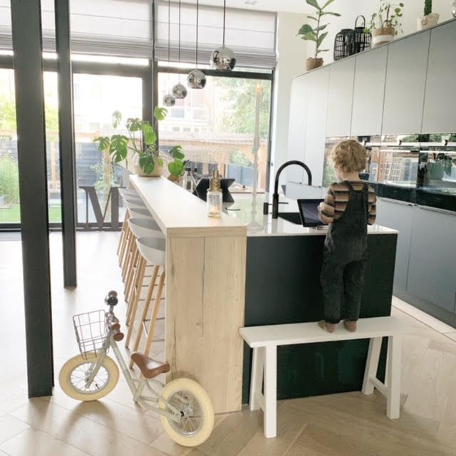 Toddler boy next to small bike in kitchen.