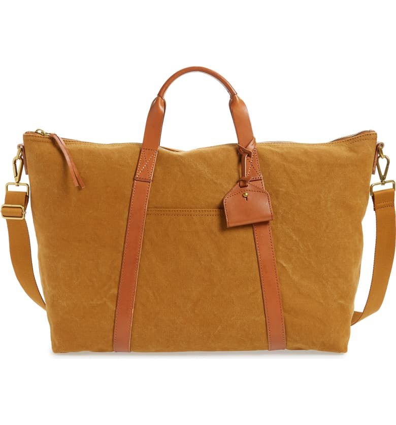 A brown canvas duffel bag with leather handles and detailing and a crossbody strap.