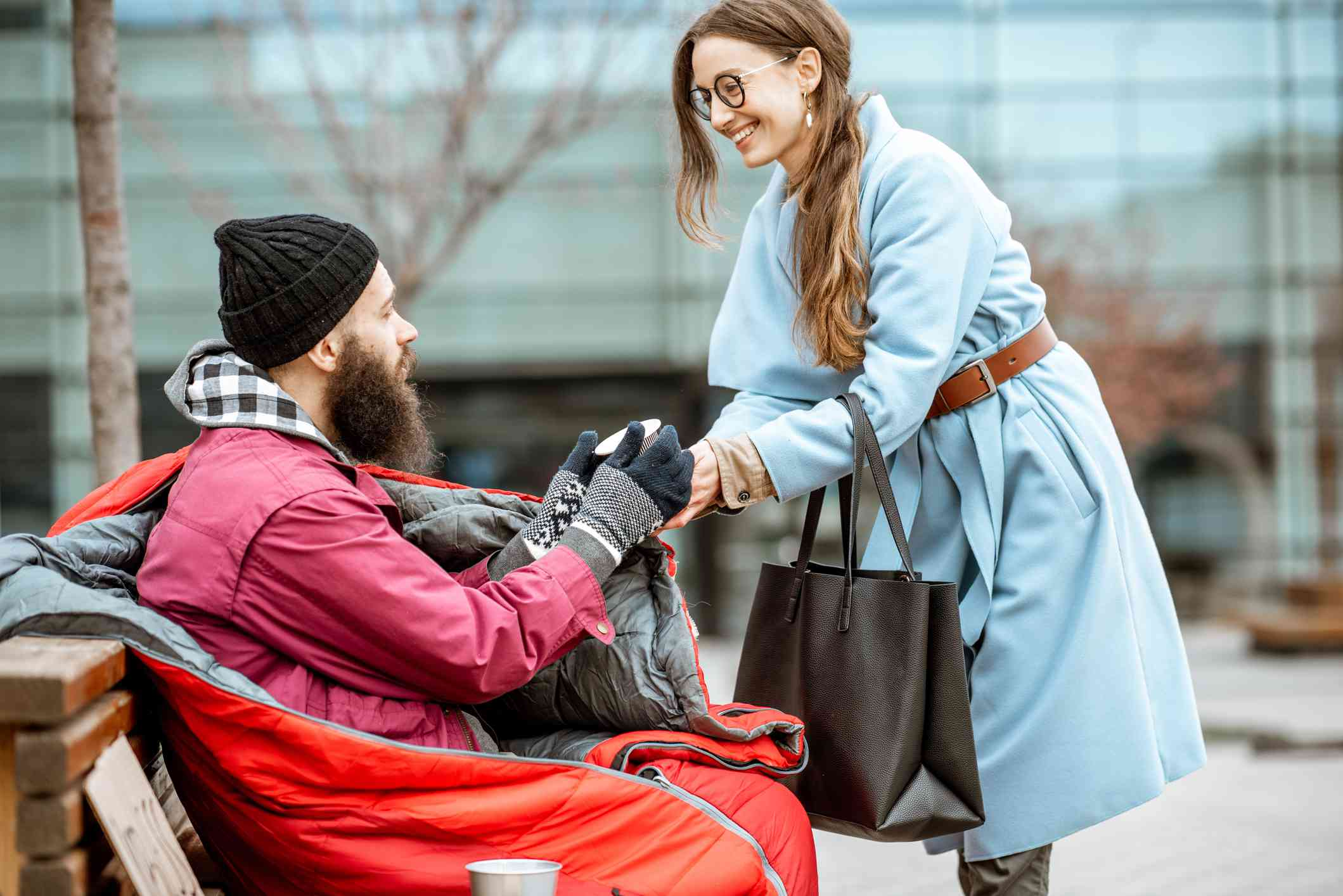 woman giving coffee to homeless man