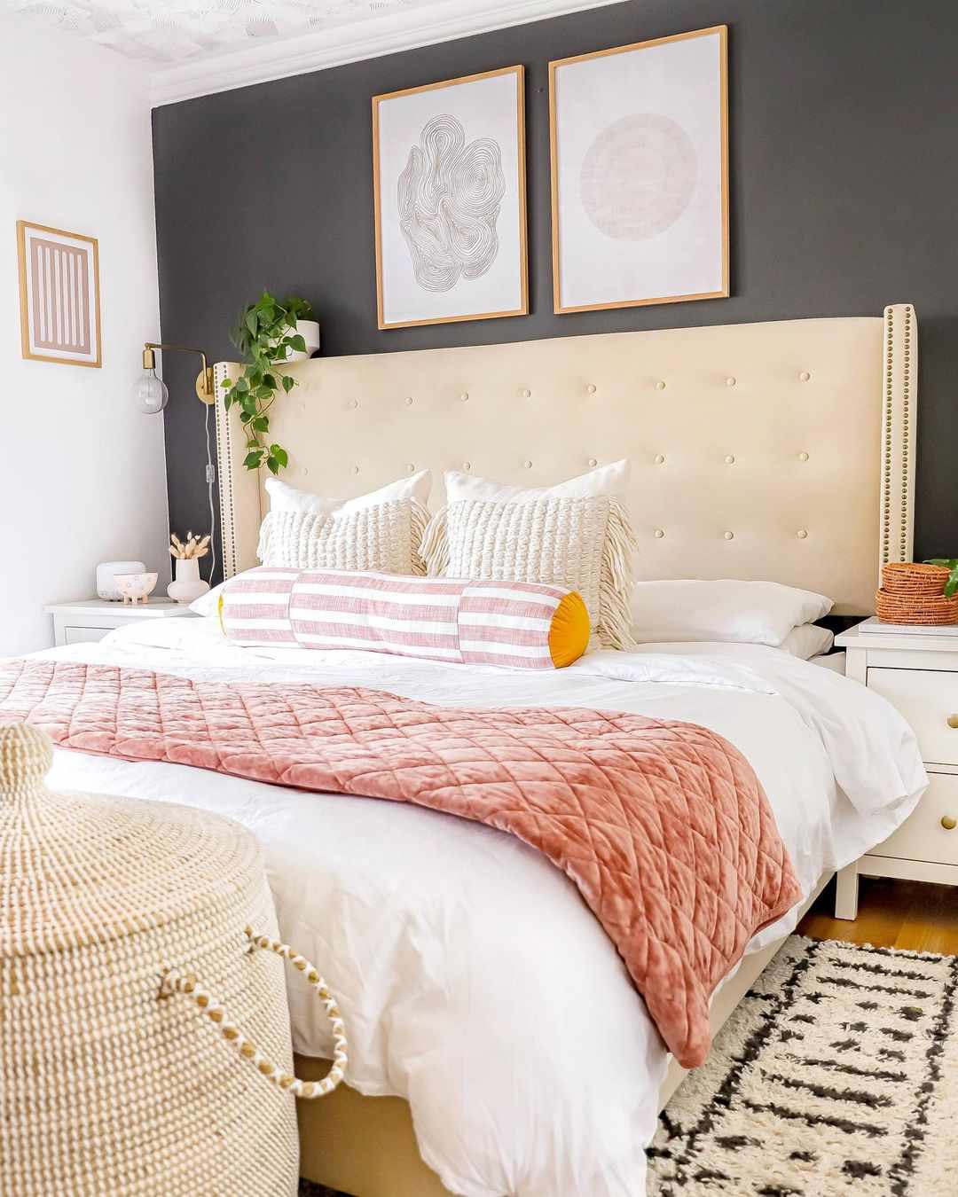 Bed with white bedding and pink quilt.