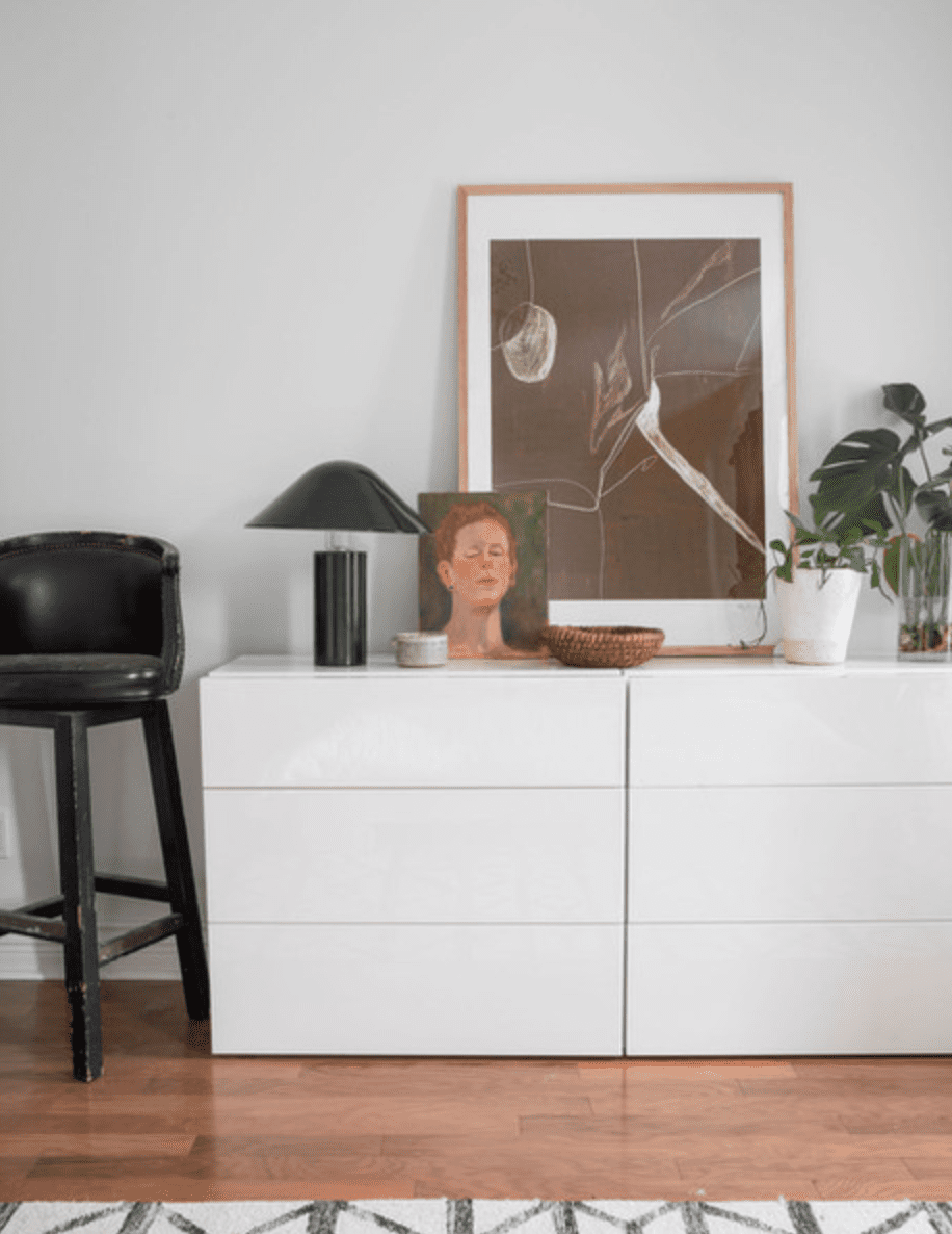 A white dresser adorned with art, plants, and other decor