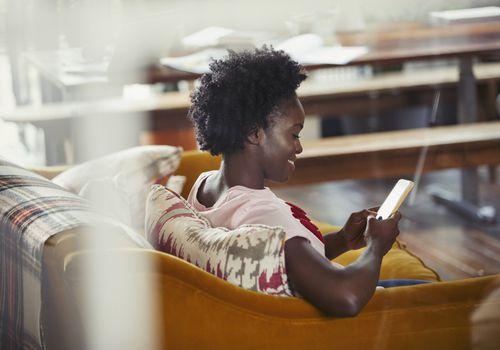 Mujer sonriente enviando mensajes de texto con el teléfono inteligente en el sofá de la sala
