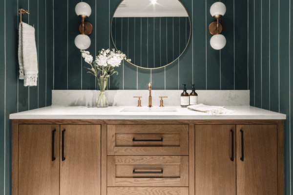 A powder room with dark green striped wallpaper, black-and-white tile floors, and other Art Deco-inspired accents