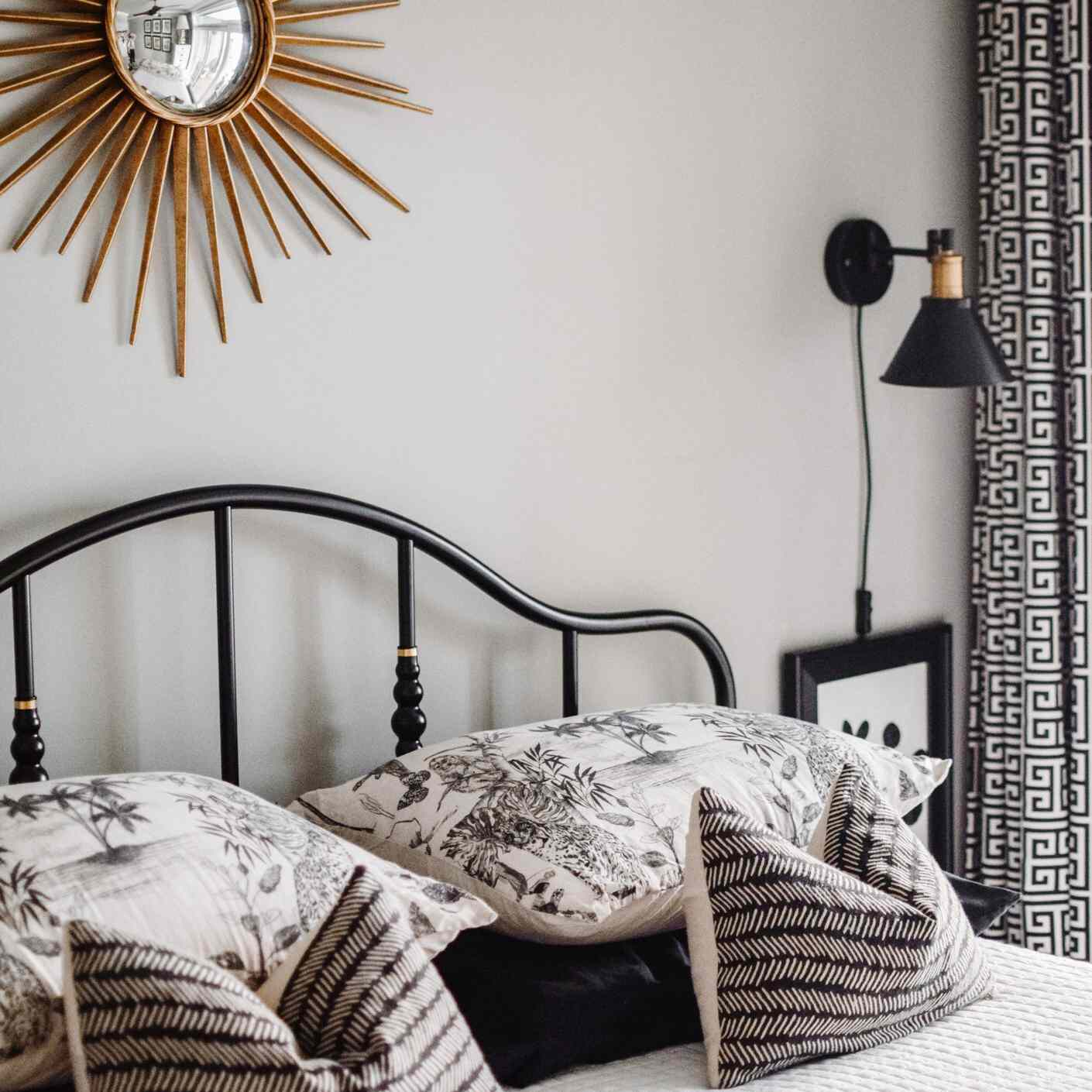 Black and white bed with large sun mirror hanging above it.
