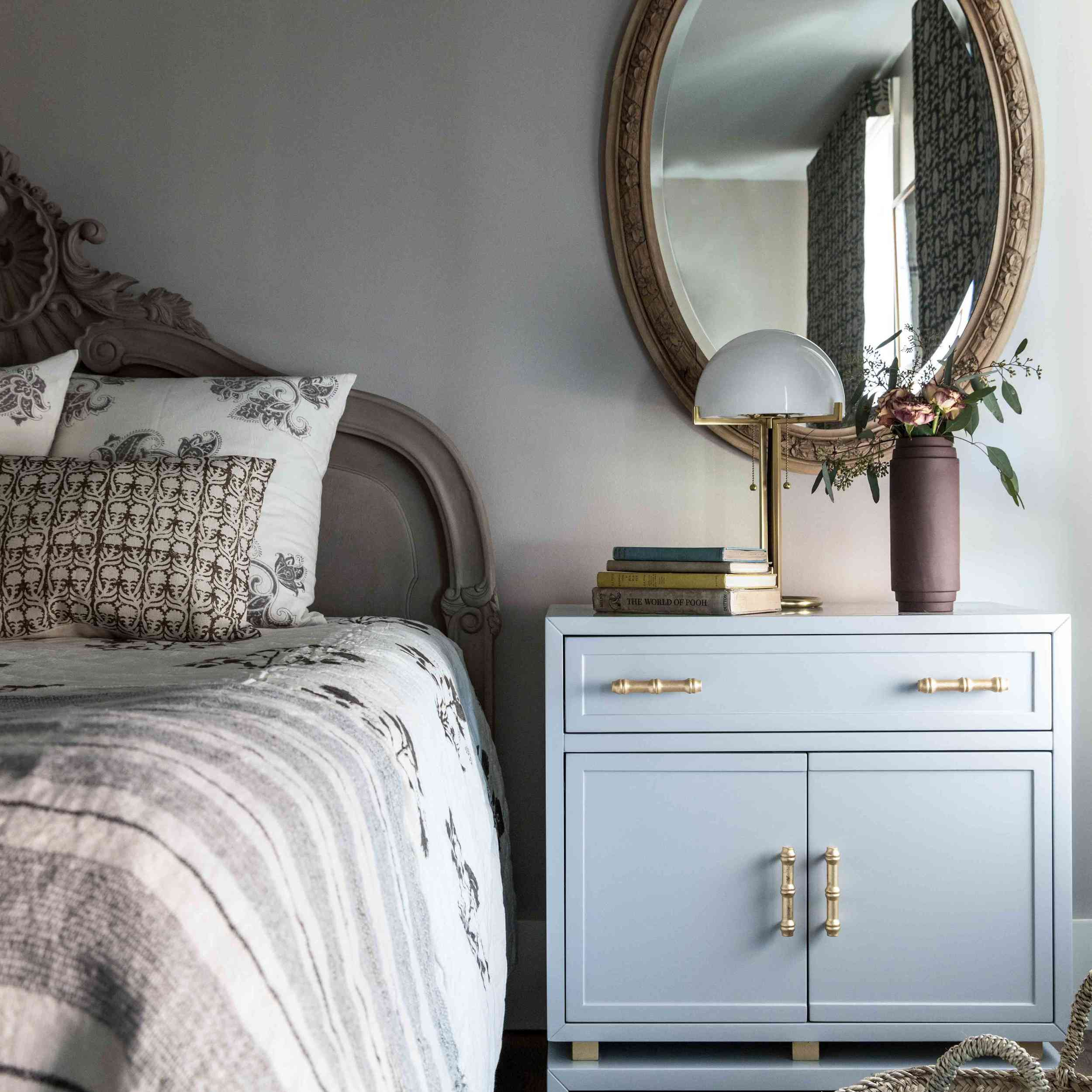 A bedroom with a Victorian headboard and mirror, as well as some more contemporary decor