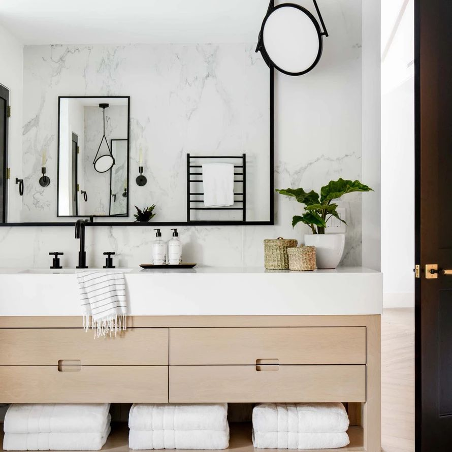 Modern bathroom with marble, matte black, and light wood
