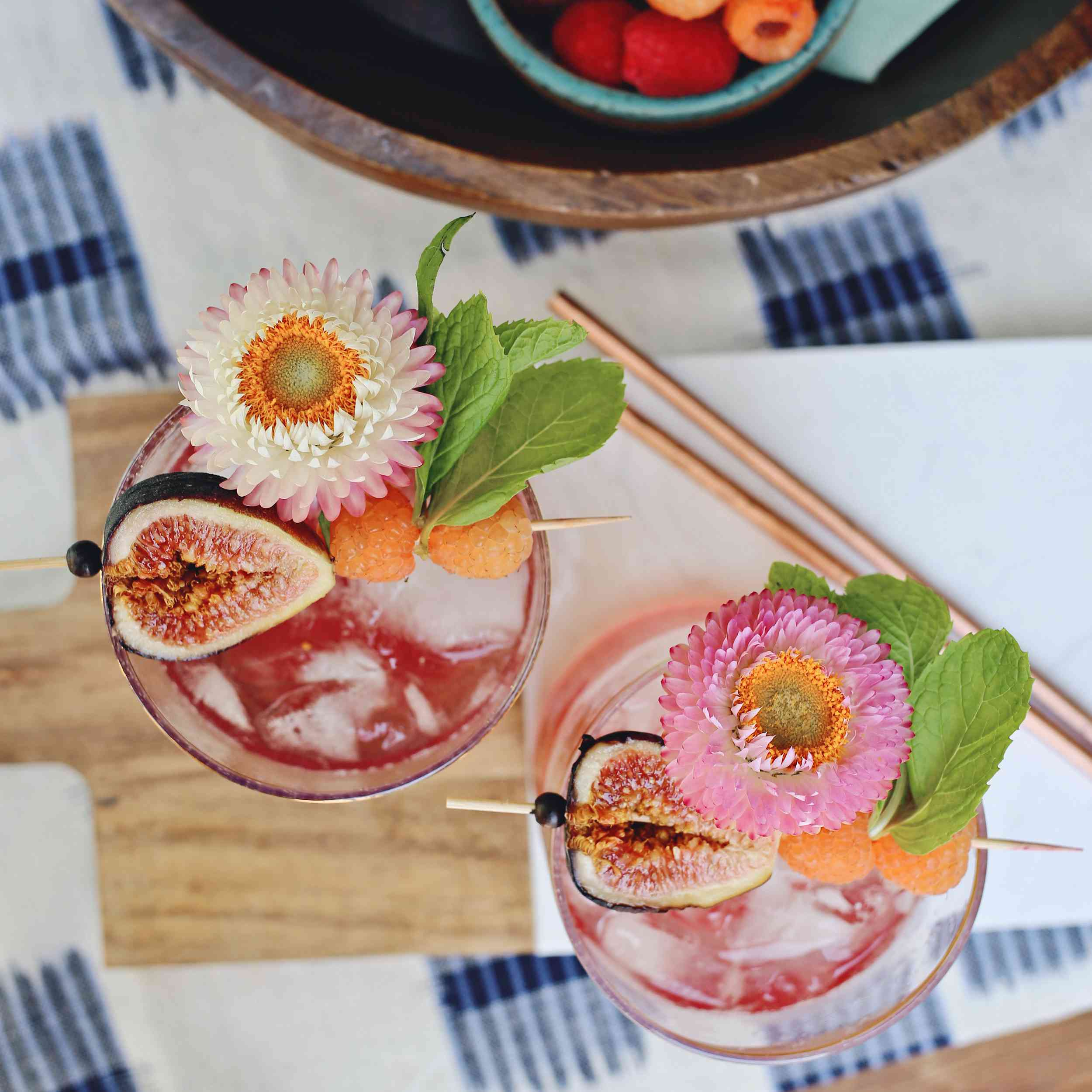 overhead view of pink cocktail with figs, raspberries and flowers on wood board and blue and white tablecloth