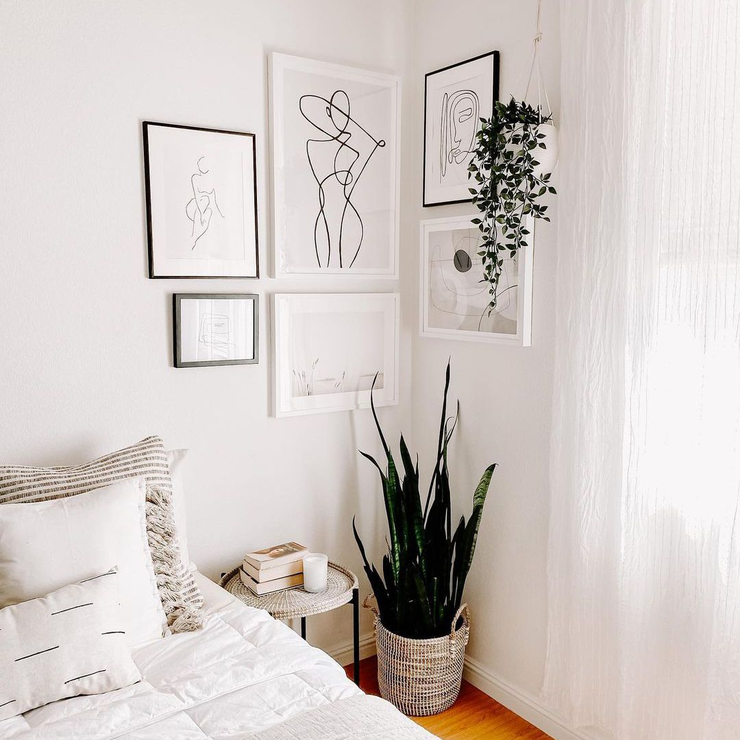 White bedroom with line art, books on side table, and plants.