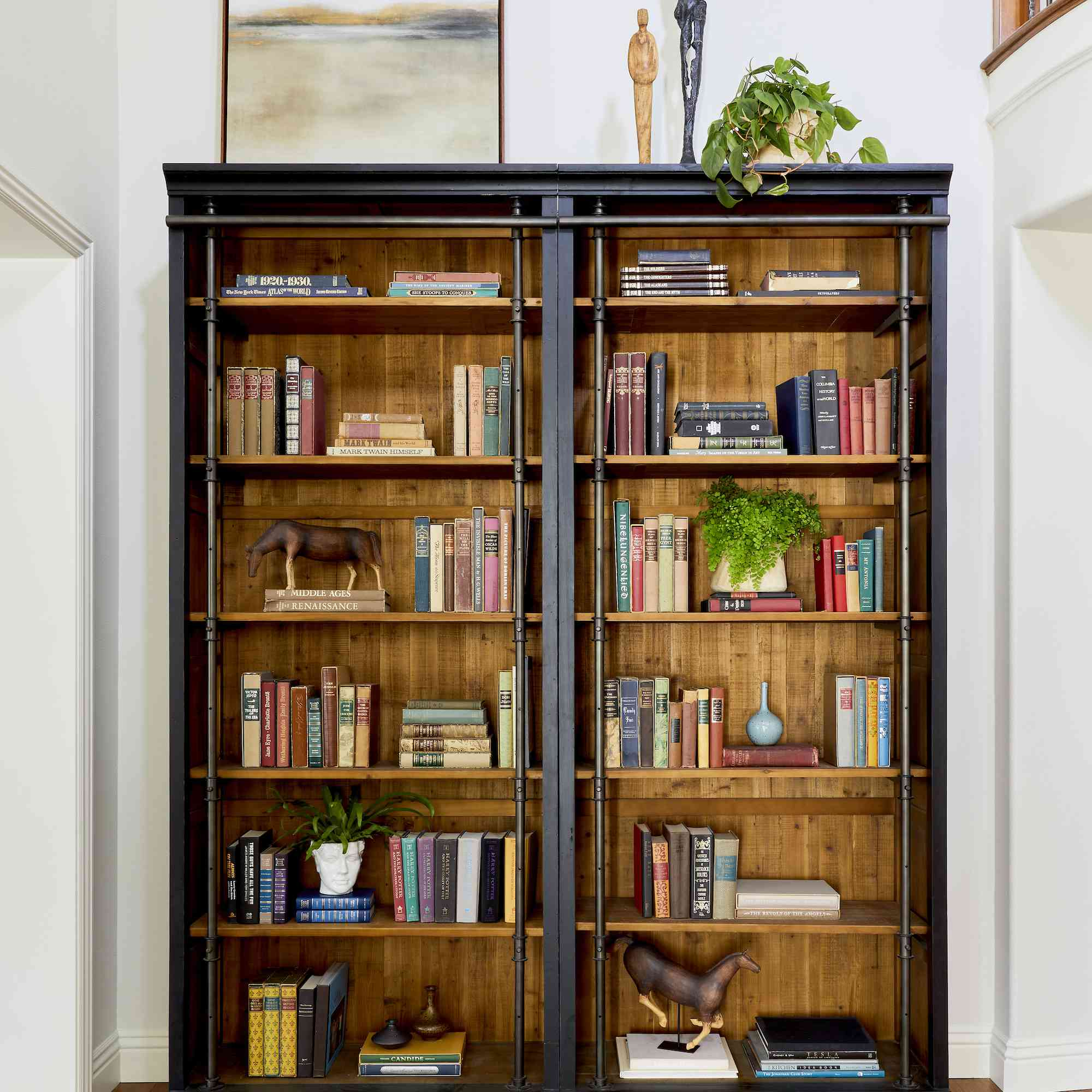Bookcase filled with antique books and decor.